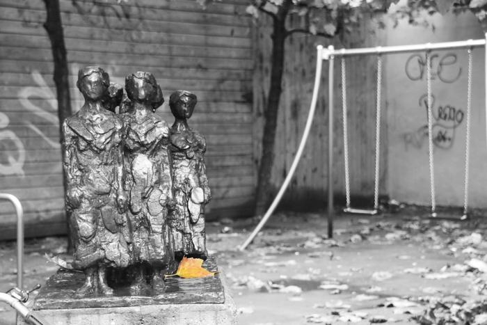 Gelbes Laubblatt am Fusse einer Figurengurppe auf dem Spielplatz, Amsterdam - Color-Key #fotoprojekt17 - diephotographin