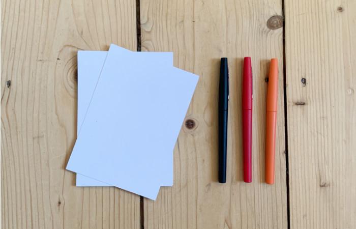 Weiße Postkarten, Filzstifte in schwarz, rot, orange - Zutaten für einfache Weihnachtskarten im Sketchnotes Stil - Increase Creativity